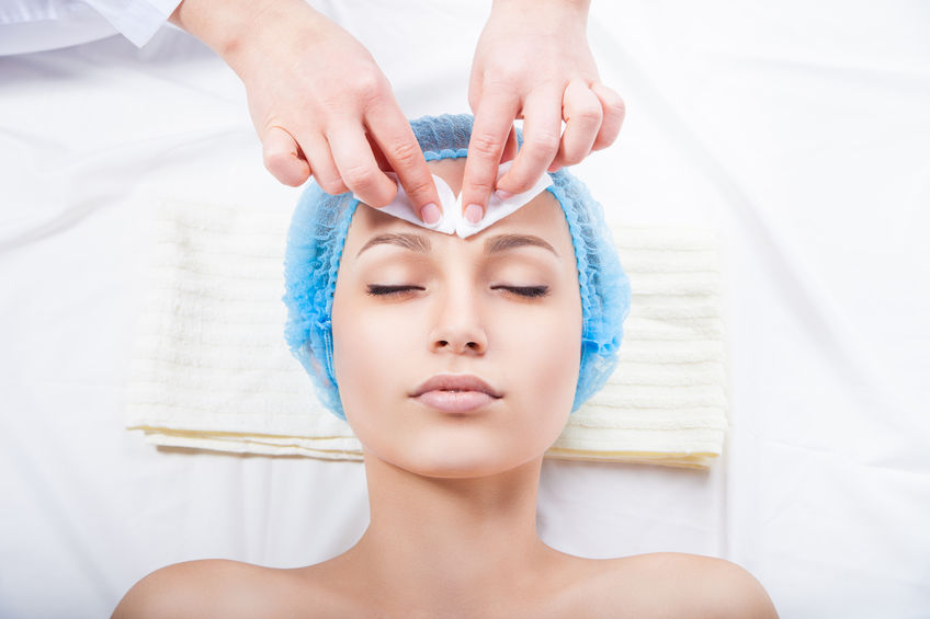 32954684 - skin care - woman cleaning face by beautician over white background